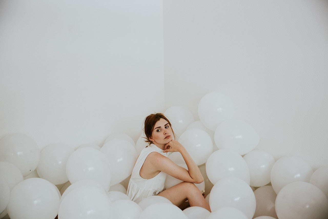 woman-sitting-amongst-white-balloons-john-taylor-watches-timepieces-blog