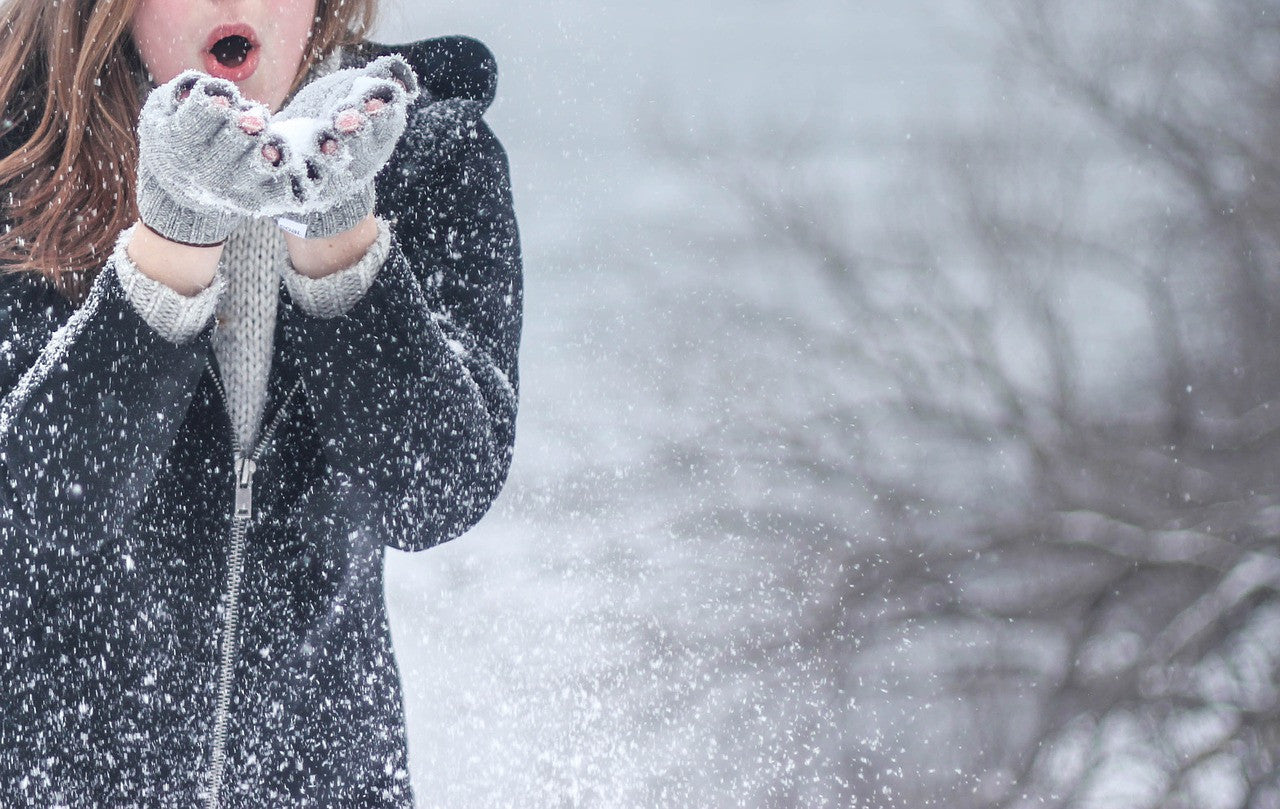 woman blowing snow on a cold day