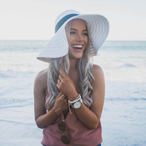 woman in hat laughing on the beach with watch on