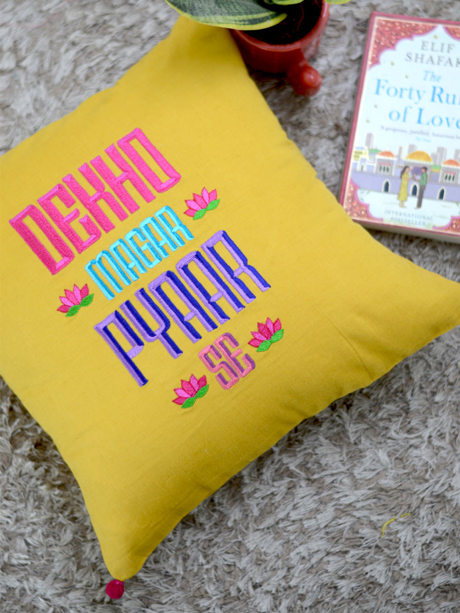 Dekho Magar Pyaar Se Cushion Cover, a hand embroidered cotton cushion cover with pom pom detailing from our wide range of quirky, bohemian home decor products like ethnic cushion covers, thread art, wall decor and more.