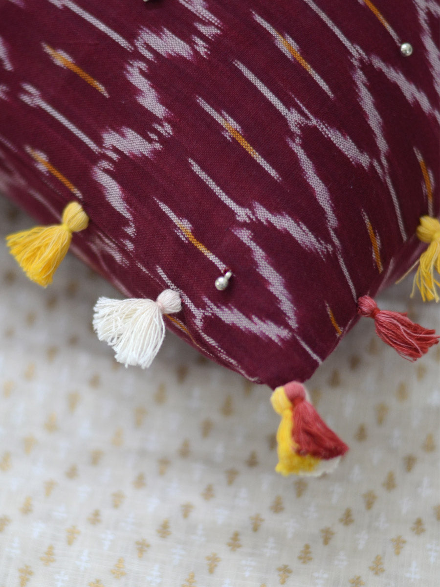 Prosperity Cushion Cover (Maroon), a unique hand embroidered cotton cushion cover with soundless ghungroo and tassel detailing from our wide range of quirky, bohemian home decor products like ethnic cushion covers, thread art and more.