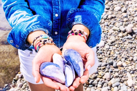 Costal girl holding clamshells showing off her semiprecious stone friendship bracelets