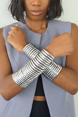 "Close up of woman wearing Silver Gladiator Cuffs in ""Wakanda Forever"" pose"