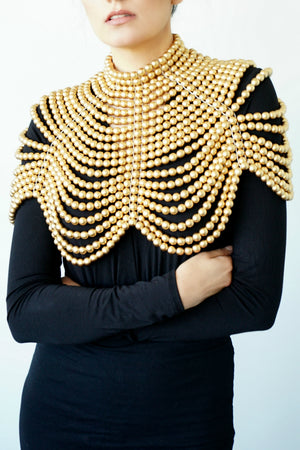 Close up of woman in a black long-sleeve dress posing with the Gold Cleopatra necklace