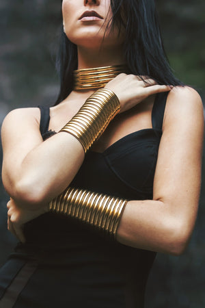 Close up of woman posing with two Gold Gladiator Cuffs and a Gold Ndebele Choker
