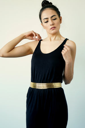 Image of woman posing with Gold Ndebele Belt wearing a black sleeveless top and black pants