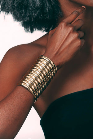 Close up of a woman wearing the Gold Ndebele Cuff and raising her arm towards her face