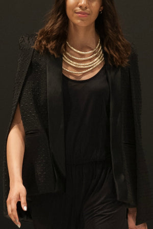 Woman walking a runway wearing the Black Cape, a Black jumpsuit and a Gold Rope Necklace