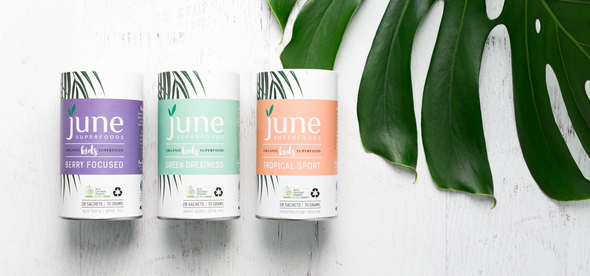 Three canisters of June Superfoods with a monstera leaf