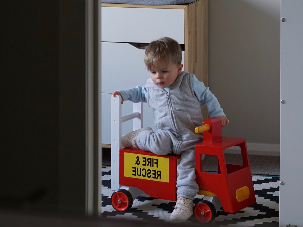 little boy on a toy firetruck in a bedroom