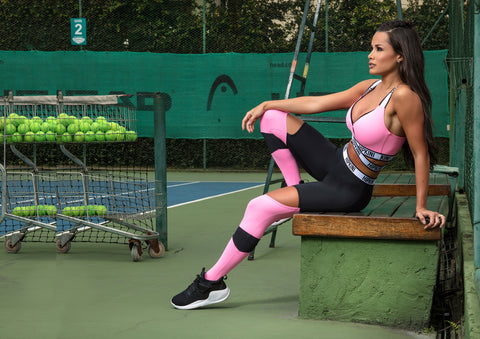 fitness model sitting on a bench on a tennis court wearing black and pink leggings and a pink fitness top