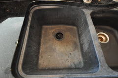 black composite granite sink with a white haze that has been etched and needs to be restored to look like new.