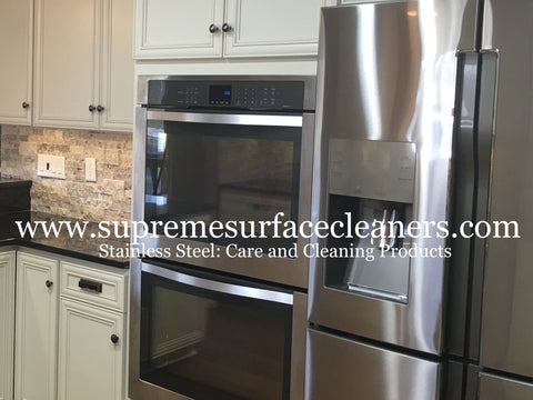 Stainless steel appliances built into cabinets with a black granite countertop.