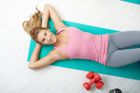 A woman lying on a yoga mat during a strenuous workout.