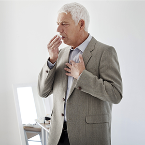 Elder gray-haired man in a gray suit coughing while covering his mouth with one hand