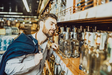 Bearded man looking at alcohol on a shelf