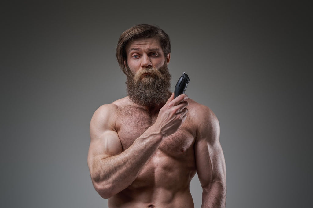 Man with beard holding a trimmer
