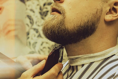 Bearded man getting a trim with electric clippers