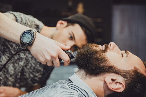 Man with long beard growth getting a trim in a barber chair