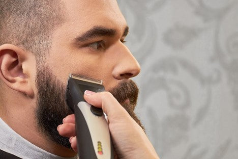 Man getting a trim to control maintain his growing beard
