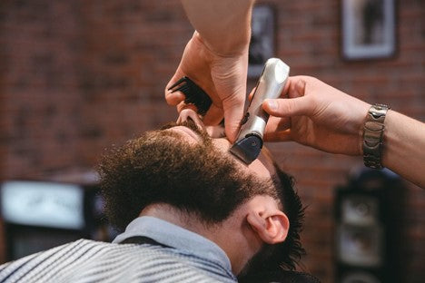 Bearded man getting his cheeks trimmed by a high quality trimmer