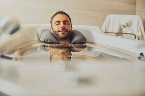 Man relaxing in a bath tub while cleaning his beard