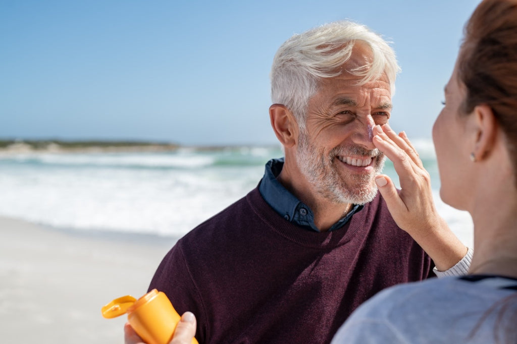 Woman applying sunscreen to the face of a bearded man