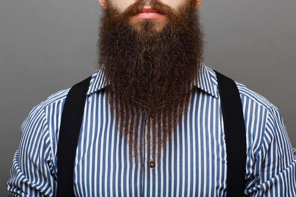 Bearded man with suspenders and a dress shirt after applying beard butter