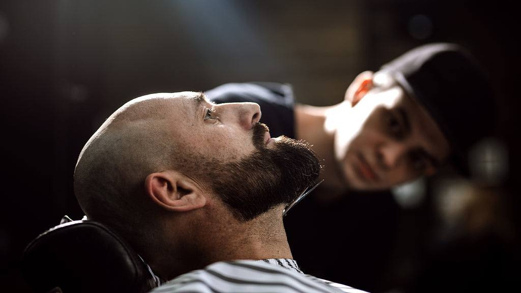 Man getting groomed in barber chair