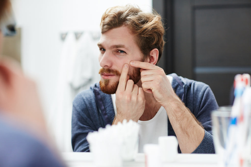 Man examining a blemish that could have been prevented by she butter in his beard