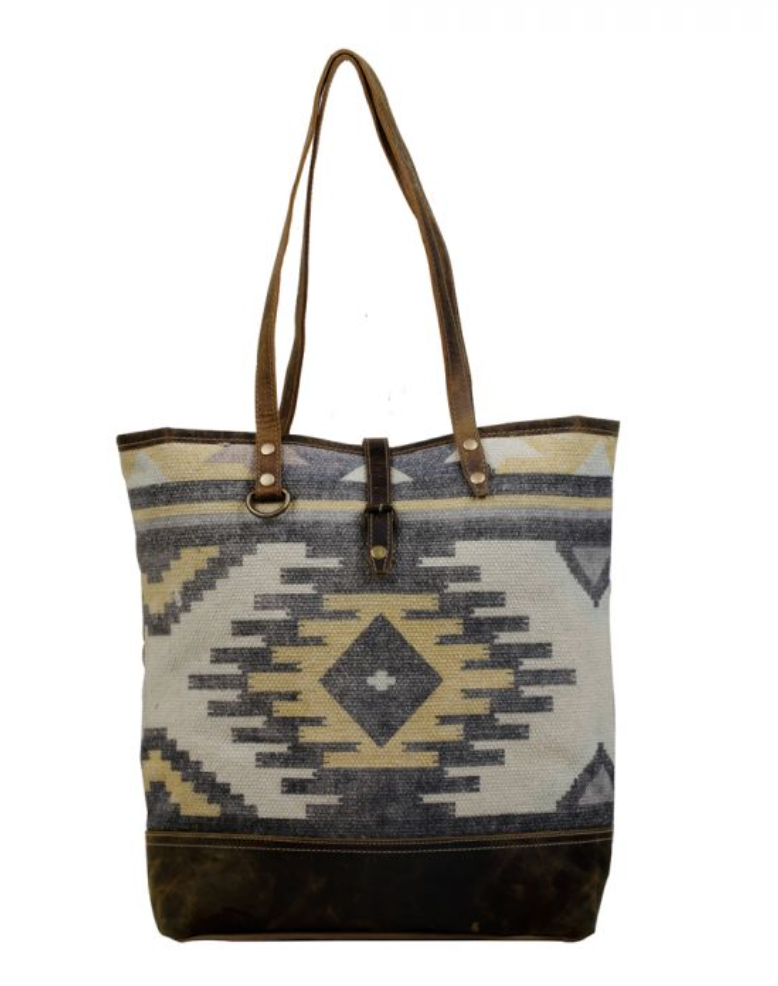 Neutral aztec-like print on a canvas bag with a pop of yellow
