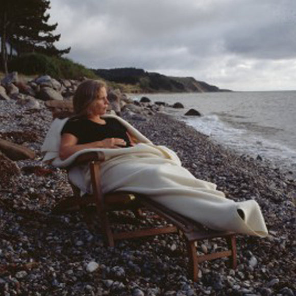 Women sitting on rocky beach wrapped in blanket