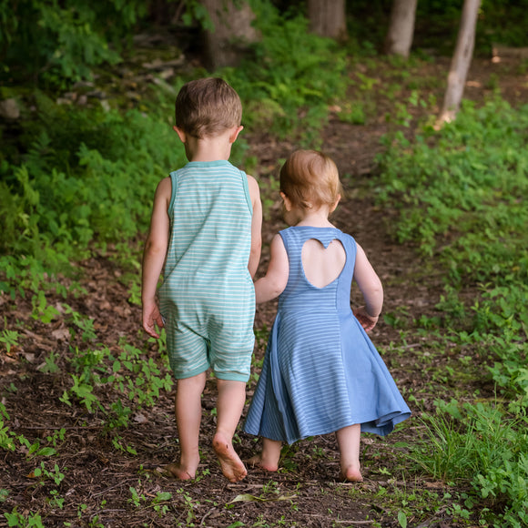 Little boy & girl walking in summer clothing as they hold hands