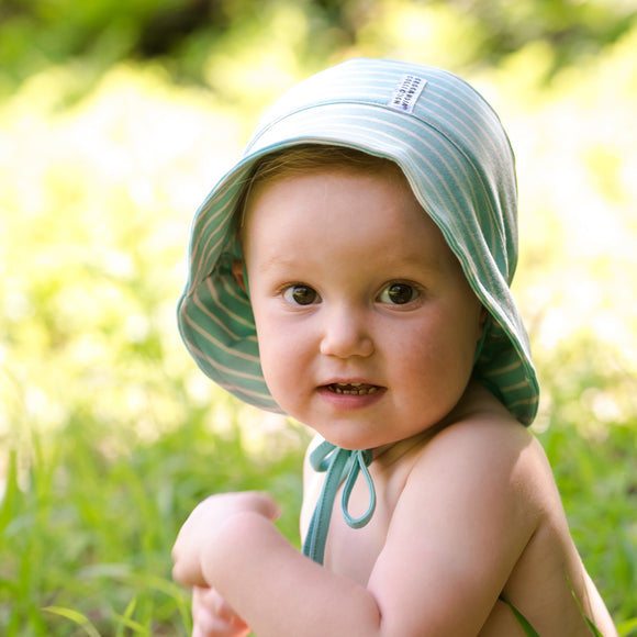 Toddler sitting in grass wearing sunhat