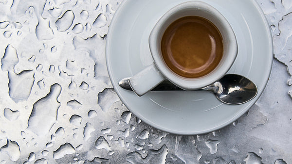 a cup of coffee with metal and water background.