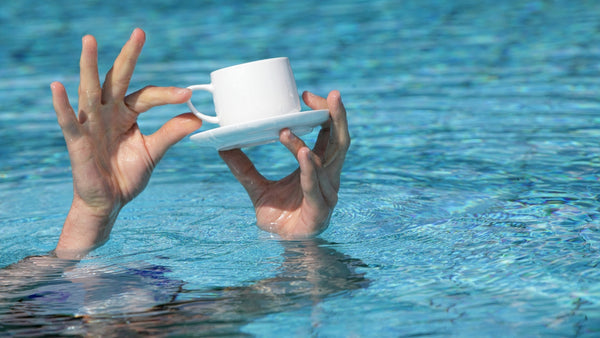 hand holding a cup of coffee in a swimming pool.