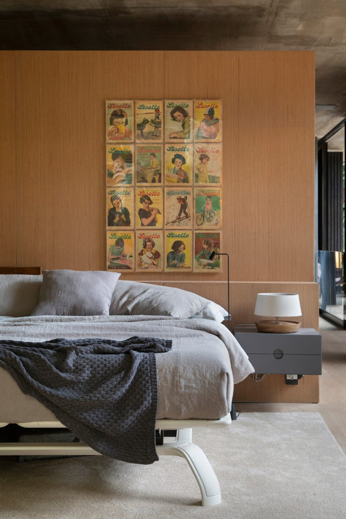 vintage magazine Lisette posters against blonde wood bedroom cladding