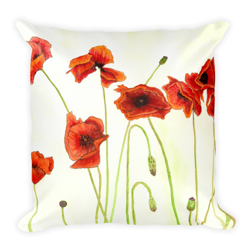 Bright watercolor painting of red poppies, green stems printed on a with pillow.
