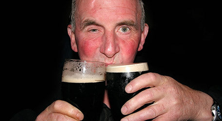 Man with alcohol flush drinking two pints of Guinness