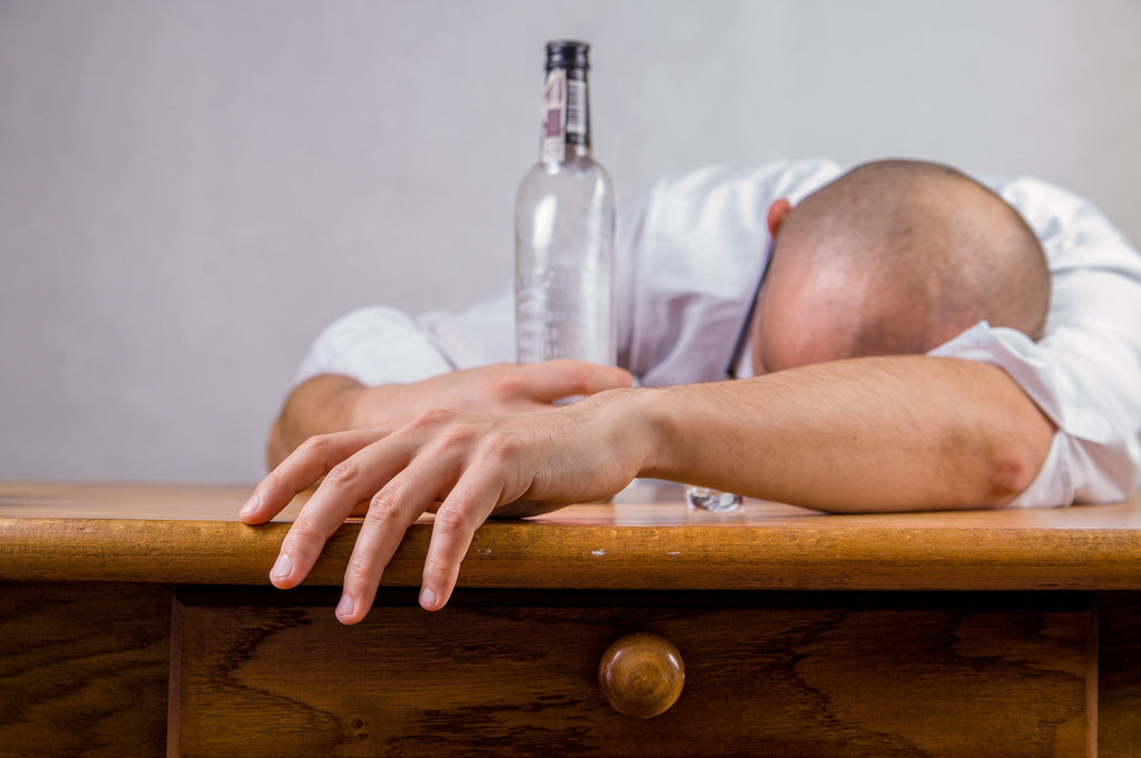 A man is hungover at a desk after drinking alcohol