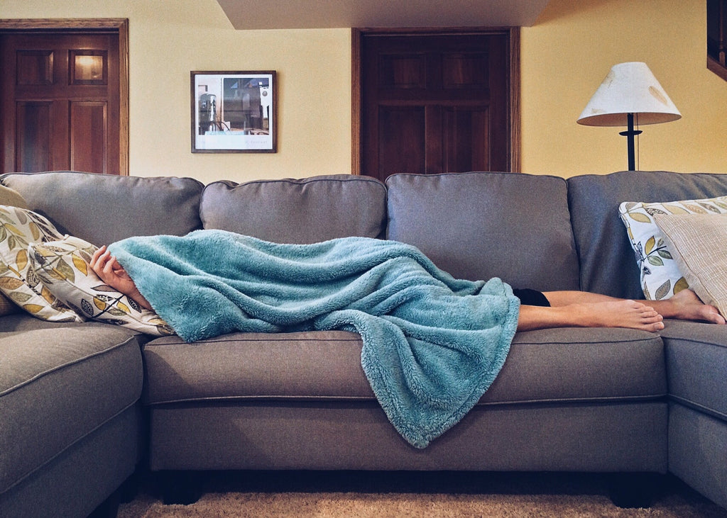 A person sleeps on a couch while being hungover from drinking alcohol