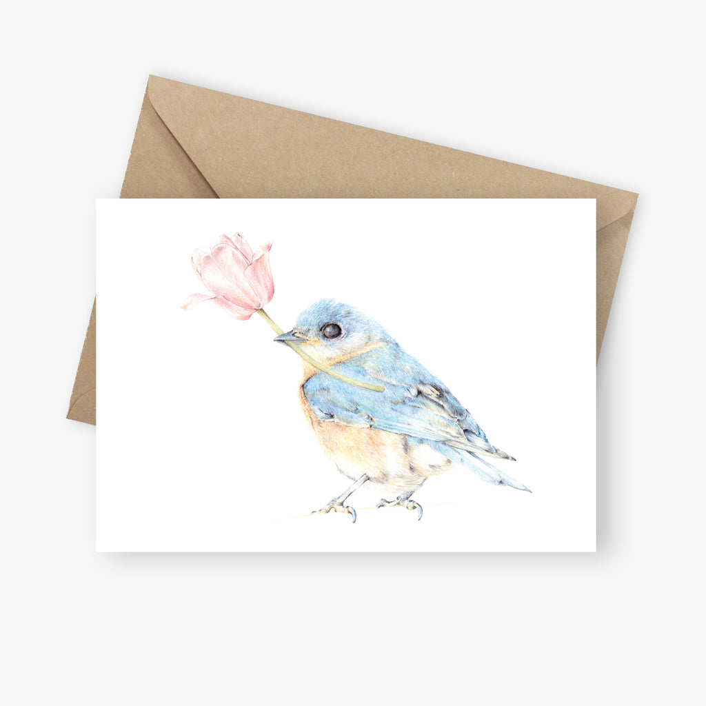 Greeting card featuring bluebird holding a pink magnolia flower.