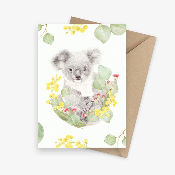 Illustrated greeting card featuring a koala sitting on an Australian native floral wreath.