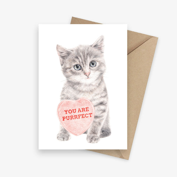 Greeting card featuring a kitten holding a big love heart.