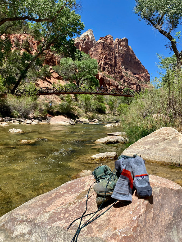 GRIP6 socks are designed for all times of the year. Pictured is a pair of socks with hiking boots on a rock in Zion National Park.