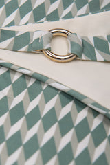Detail of ring bikini bottom in green geometric sage print by Caroline af Rosenborg