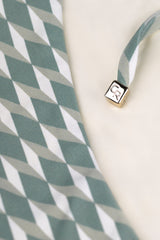 Cube detail side tie green bikini bottom triangle shape in cream white geometric tile print by Caroline af Rosenborg