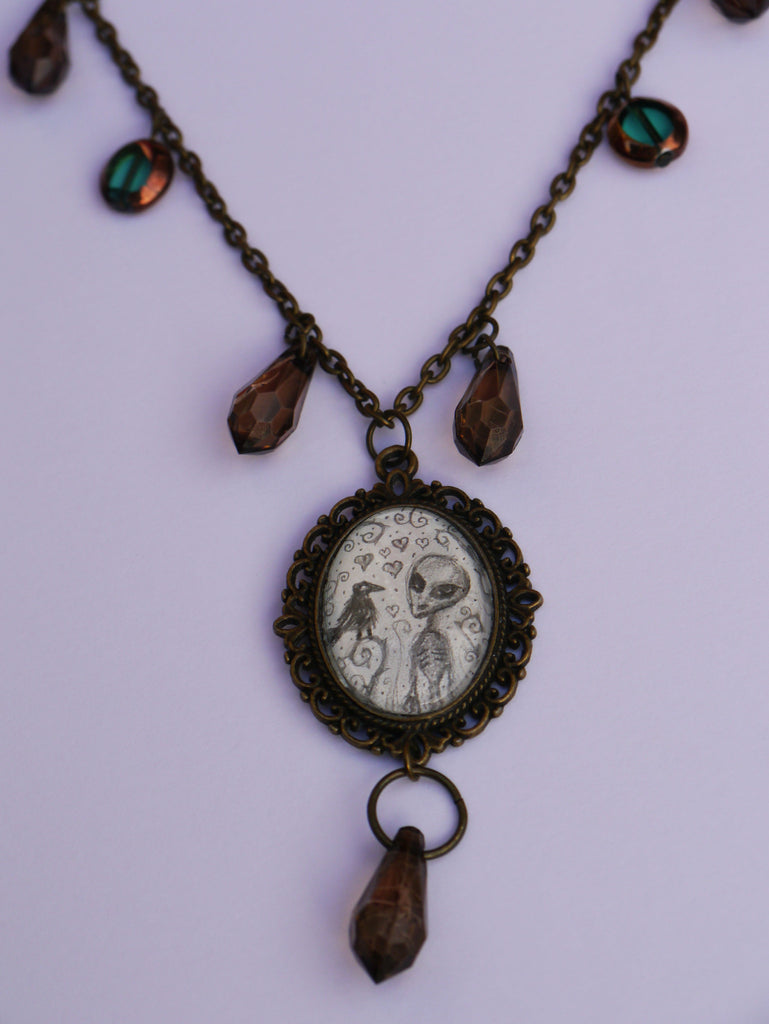 Close up image of Alien and Crow necklace