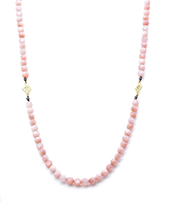 "The lovely soft peach tones of the faceted moonstones is so flattering and versatile. The moonstone beads are 8mm in diameter. 18k yellow gold scroll stations add brightness. The necklace is 36"" long and fastens with a toggle clasp."