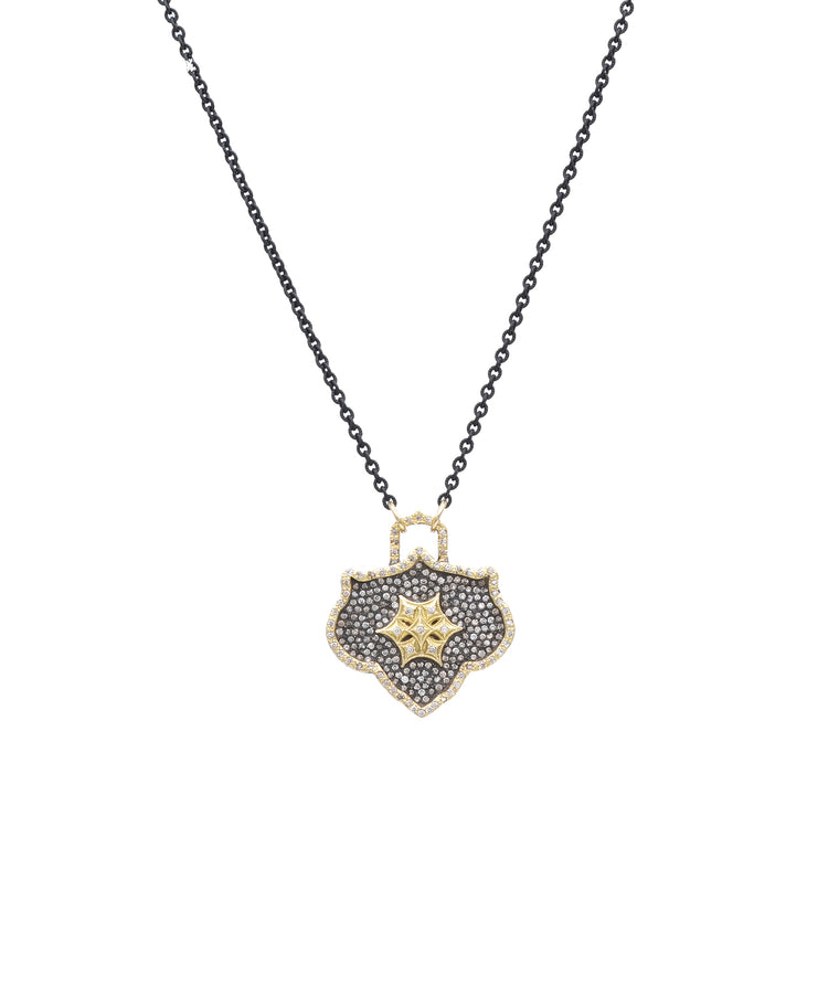 "This pendant is set with champagne diamonds for a warm look. The 18k yellow gold and sterling silver pendant is 1"" across and hangs from an adjustable 18"" silver chain."